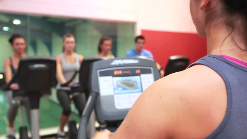 Trainer teaching spin class in gym