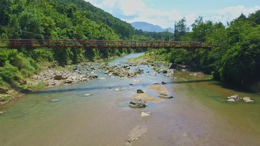 flycam moves under car bridge above peaceful green river among stones against pictorial highlands and blue sky