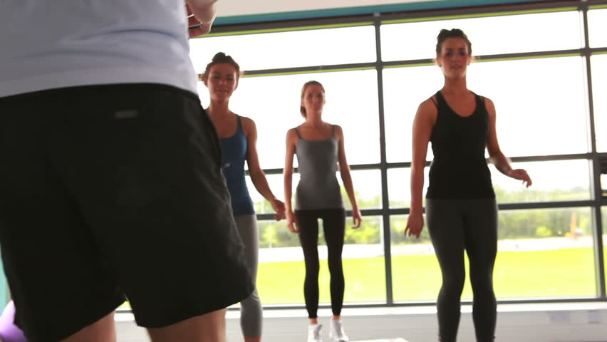 Trainer with his female aerobic group in gym
