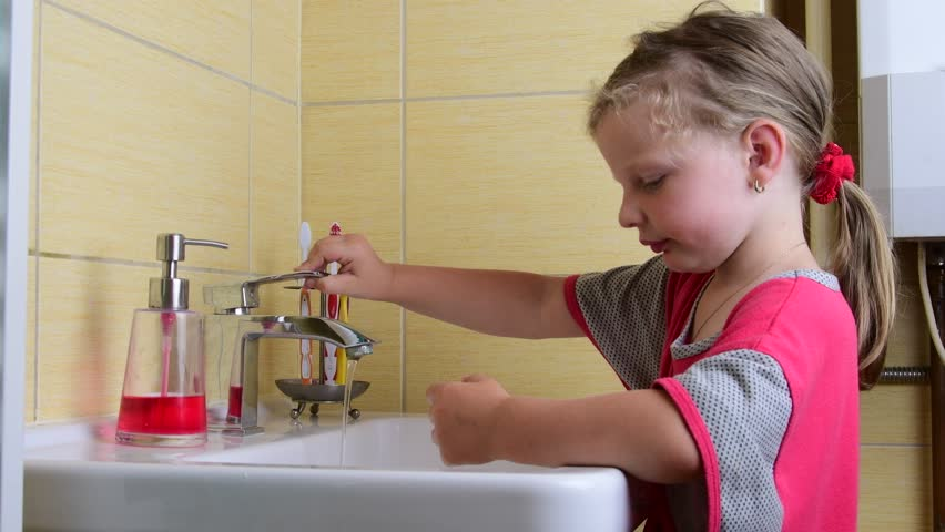 Sweet little girl washes her hands in the bathroom. Preschool concept, childhood concept. Cute girl wears nightdress.