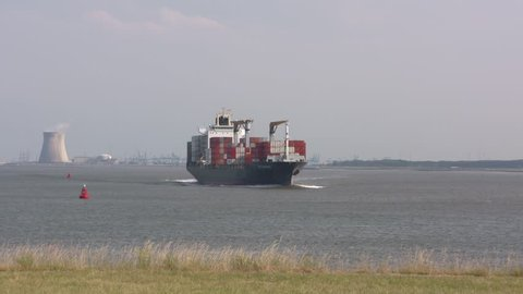 BATH, NETHERLANDS - JUNE 2017: Container ship Cap Beatrice navigates on the Western Scheldt, in The Bocht van Bath (the curve of Bath). Cooling towers of the nuclear power plant Doel in background.