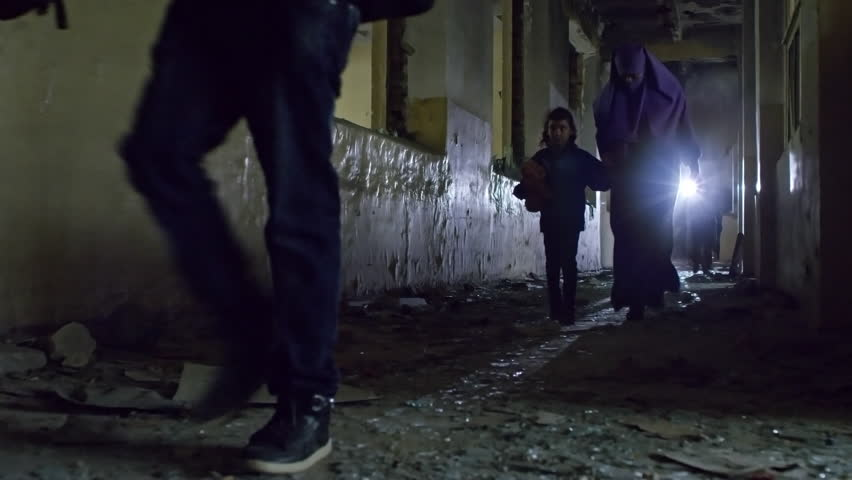 PAN with low angle of group of male refugees and Muslim woman in niqab holding hand of little girl walking along dirty floor in dark abandoned building; unrecognizable soldiers in background