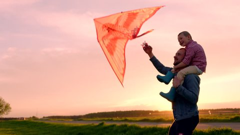 Close up little boy sitting on his daddy's neck and launching flying kite at sunset