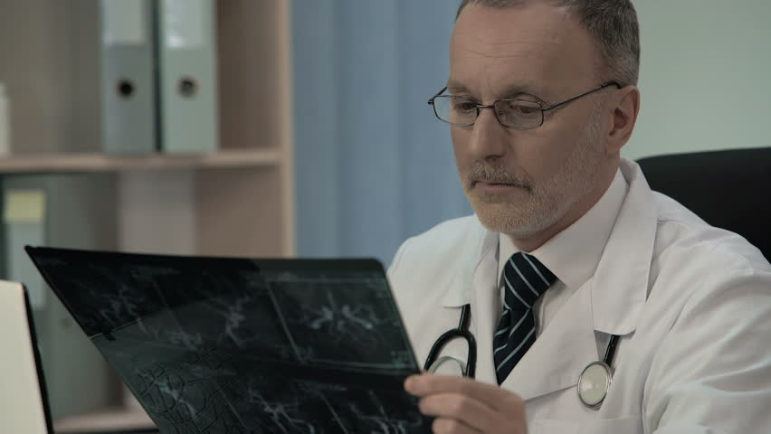 Neurologist examining patient venogram and typing his findings in patient card