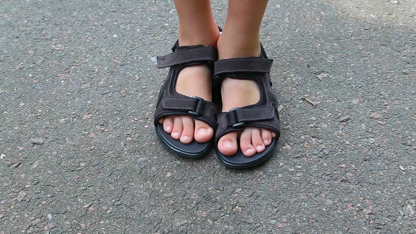 Closeup top view of feet of white child wearing brown leather sandals with black rubber soles isolated on grey urban pavement background. Real time full hd video footage.
