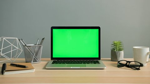 View of laptop with green screen on the office table. Chroma key. Close up shot.