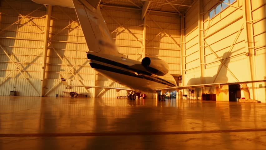 Beautiful pan of private jets parked in aircraft hangar and outside during Sunset