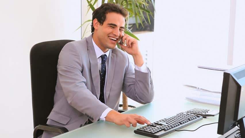 Business man sits in front of his computer typing while he makes a call