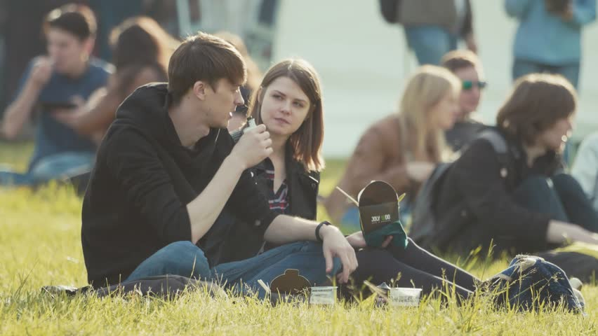 SAINT PETERSBURG, RUSSIA - JUNE 24, 2017: Young caucasian couple sitting on grass, talking at festival. Man smoking vape, girl holding box of noodles. Summer sunny day in city park