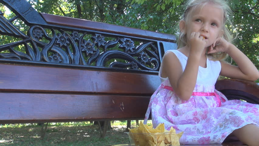 Little Girl Eating Cornflakes on a Bench in Park, Child Feeding Herself