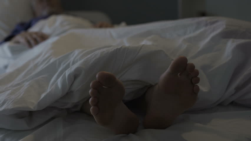 Sleeping man scratching his feet, nasty smell and discomfort due to foot fungus