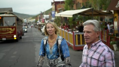 Attractive senior caucasian couple walk on historic Main Street with trolley in background, Park City, Utah at dusk.