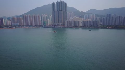 Aerial POV fly over Victoria Harbour waters to dense developed Shau Kei Wan and Sai Wan Ho areas of Hong Kong island, small motor boat on way. Very tall residential buildings in middle, many towers