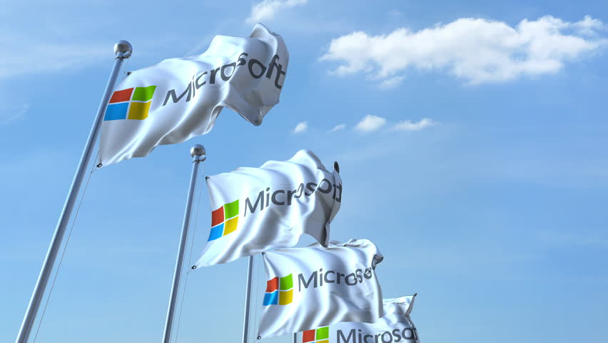Waving flags with Microsoft logo against sky, seamless loop. 4K editorial animation