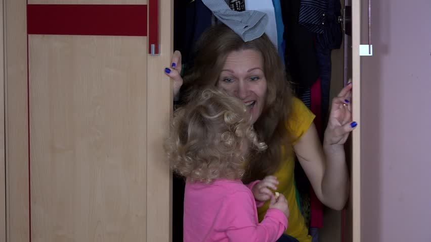 Toddler girl find her mother in closet. Happy child play with mom. Static closeup shot. 4K UHD