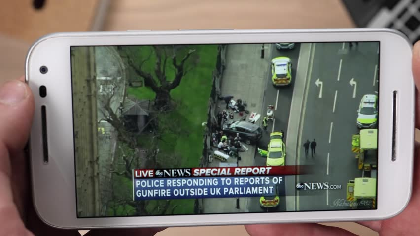 Watching the news on a smartphone showing live coverage of a terrorist attack.
