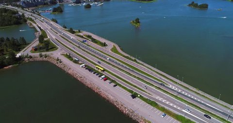 Bus on a highway, Cinema 4k aerial pan view following a yellow coach on a road 51 motorway, just outside Helsinki, at a sunny day, in Uusimaa, Finland