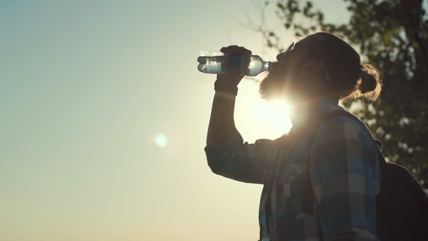 Side view of stylish man with backpack drinking water from bottle on background of sunlight and nature. Slow motion. | Shutterstock HD Video #29966929