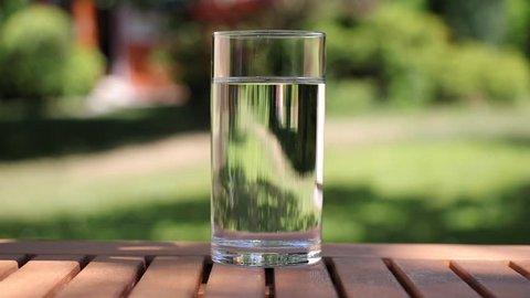 Sparkling tablet in a glass of water. Aspirin splash, headache solution on blurred garden background.