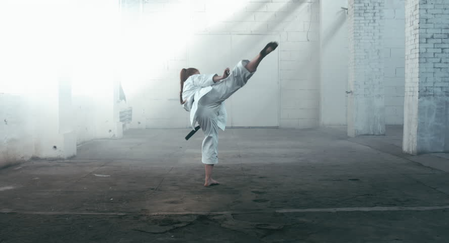 MED Caucasian professional female athlete wearing kimono practicing karate in abandoned warehouse, DX shot. 4K UHD, 60 FPS SLO MO