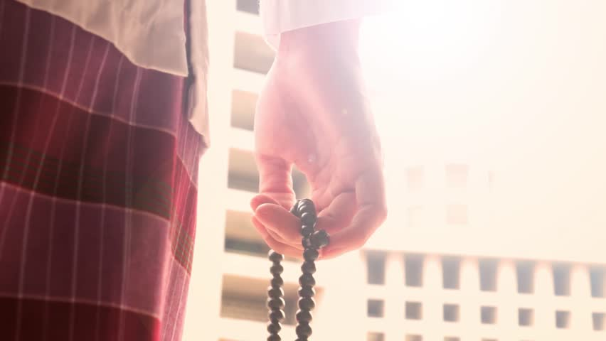 Video footage of muslim hand counting a prayer beads in the Istiqlal mosque while praying to the God