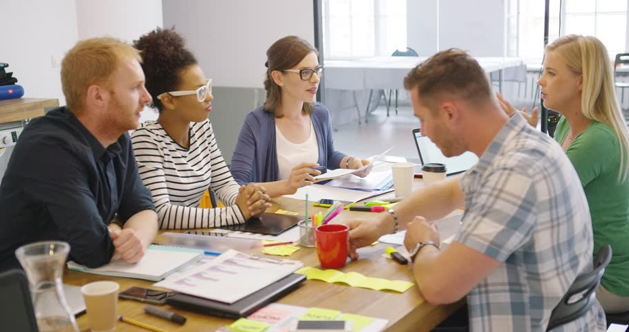 Diverse group of young colleagues having fun while working together at table in modern office and brainstorming in new ideas. | Shutterstock HD Video #29996689
