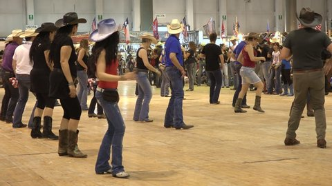 Cremona, Italy, May 2017 -  People dancing country line dance at a folk event, cowboy USA style. Men and women having fun choreography American horse festival. Music tradition jeans boots and flag