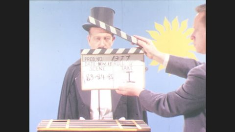 1970s: UNITED STATES: clapper board in front of magician on set. Magician stands in clothing. Magician takes off hat. Snow falls