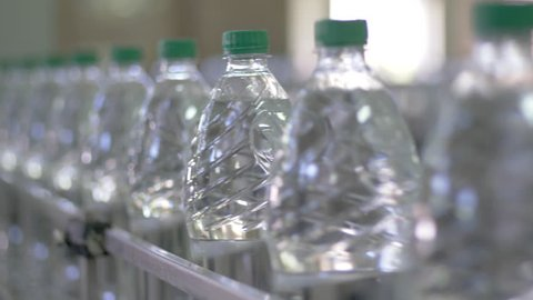 Automatic conveyor line for bottling mineral water in the plastic bottle. Line for PET bottle water. Water factory-bottling pure spring water into bottles. Selective focus.