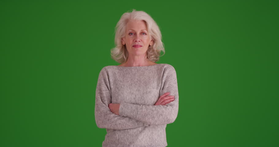 Portrait of mature woman in her 50s smiling at camera with arms crossed on greenscreen. Lovely elder woman looking at camera confidently on green screen to be keyed or composited. | Shutterstock HD Video #30024379