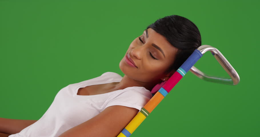Lovely African American female in her 20s lounging on chair on green screen. On green screen to be keyed or composited.