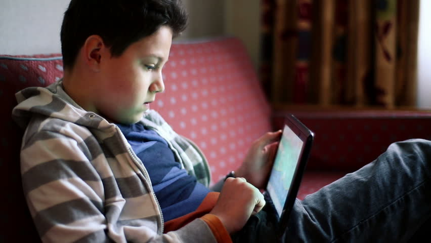 Young teenager playing games on tablet computer