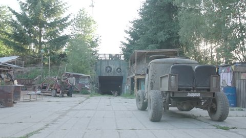 Post apocalyptic car arrive to post apocalyptic city. Slow motion, s-log, ungraded