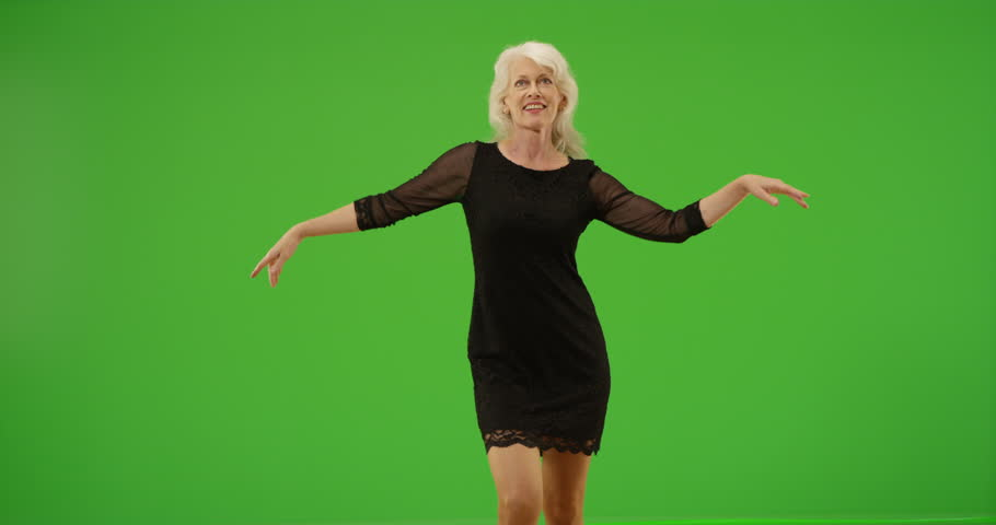 Happy senior woman dancing in a black dress on green screen. On green screen to be keyed or composited. #30063409