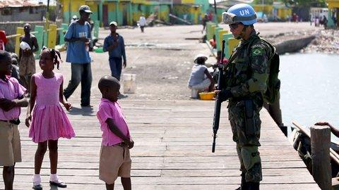 A UN soldier shakes a little Haitian boy's hand