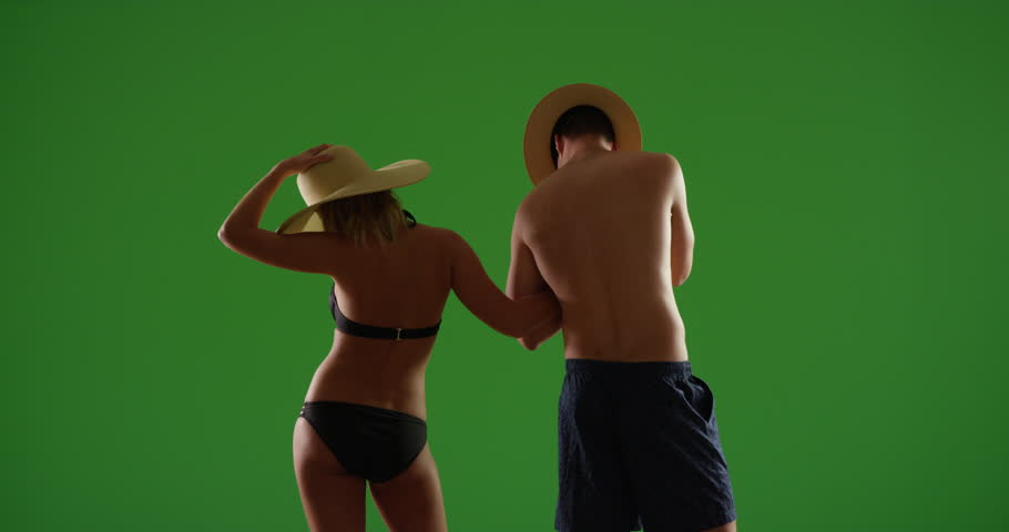 Happy millennial couple having fun watching the sunset on green screen. On green screen to be keyed or composited.