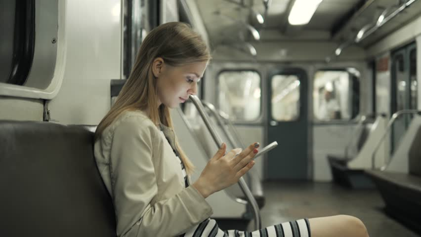 Young woman listening to music on train using tablet computer, student girl after lessons in subway wagon with laptop pc public wi fi, transportation for yong travellers