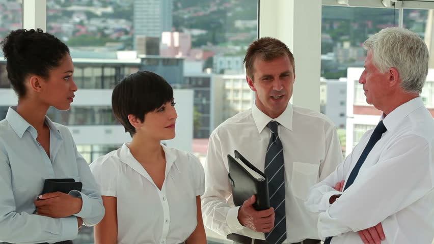 Business people talking while standing in a bright room | Shutterstock HD Video #3008779