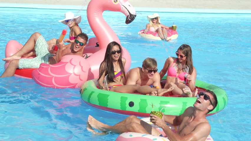 SLOW MOTION CLOSE UP Happy smiling students have water gun fight on colorful floaties at pool party on spring break. Cheerful young people having fun on inflatable flamingo, watermelon and doughnut