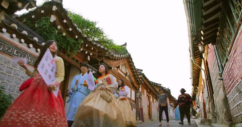 Korean Girls dressed Hanbok in traditional dress walking at Bukchon Hanok village in Seoul, South Korea. Hanok is a term to describe Korean traditional houses.