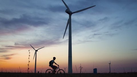 A young man on a bicycle rides past a wind power plant at sunset