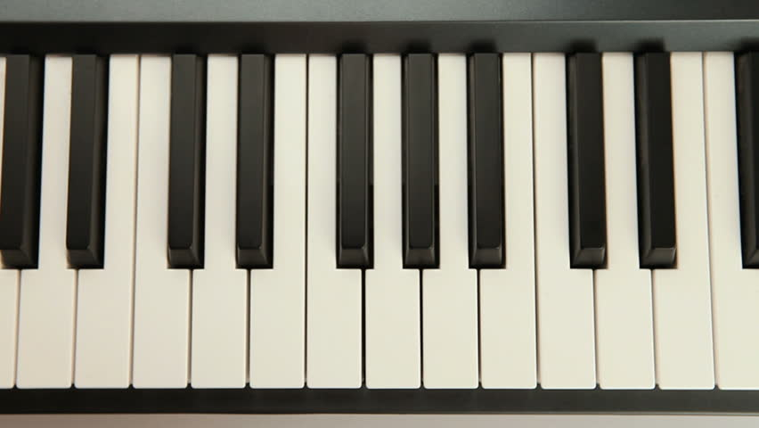 Hand playing piano in a studio