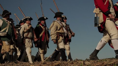 VIRGINIA - OCTOBER 2016 - Reenactment, large-scale, epic American Revolutionary War anniversary recreation -- U.S. Continental Army Soldiers in formation marching as on parade with Muskets, flags.