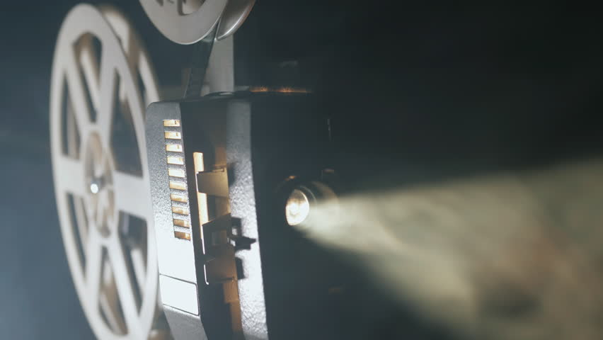 Front view of an old-fashioned antique Super 8mm film projector, projecting a beam of light in a dark room next to a stack of unraveled film reels. | Shutterstock HD Video #30171919