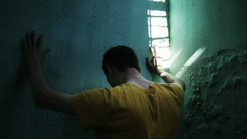 The prisoner is in the dark prison. Humility and peace of man. A man prays
