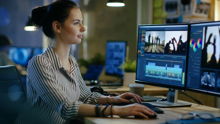 Female Video Editor Works with Footage and Sound on Her Personal Computer, She Turns and Warmly Smiles into the Camera. Her Office is Modern and Creative Loft Studio. Shot on RED EPIC-W 8K  Camera. | Shutterstock HD Video #30236119