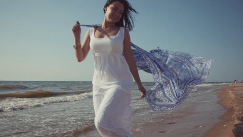 Gypsy young brunette girl wearing white maxi long dress running near sea or ocean windy beach with mandala silk scarf in hands.Bohemian style. Boho lifestyle.Slow motion.Film tonned