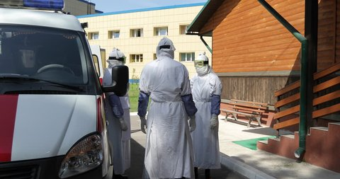 Threat of the epidemic or infection. Group of doctors or nurses wearing full Ebola virus protection uniform  standing near ambulance car and talking. Evacuation and disinfection. 4K footage.