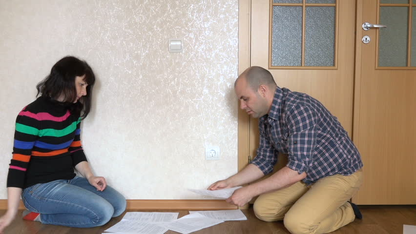 Married couple sitting on the floor discussing documents and contracts. Man and woman look at unpaid bills. Communal payments, Utilities, unpaid bills. Loan agreements.
