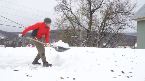 Man with a shovel removing snow from a roof. Caucasian men using to shovel heavy snow off roof.  People with plastic shovel tool push clean snow from roof.